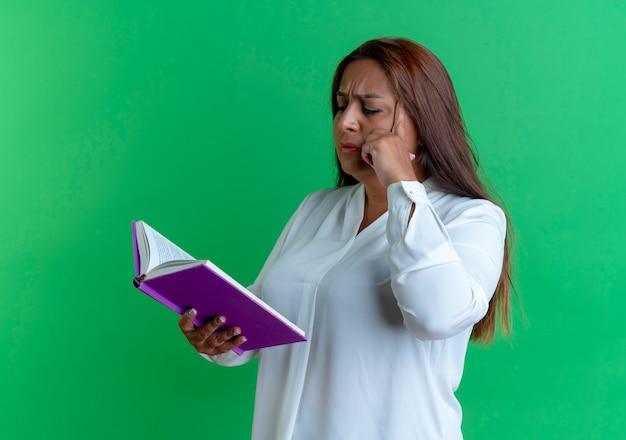 Denken casual blanke vrouw van middelbare leeftijd houden en kijken naar boek en zetten vinger op voorhoofd geïsoleerd op groene muur