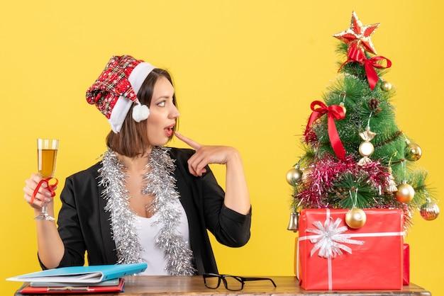 Denken charmante dame in pak met kerstman hoed en nieuwe jaar decoraties met wijn in het kantoor op geel geïsoleerd