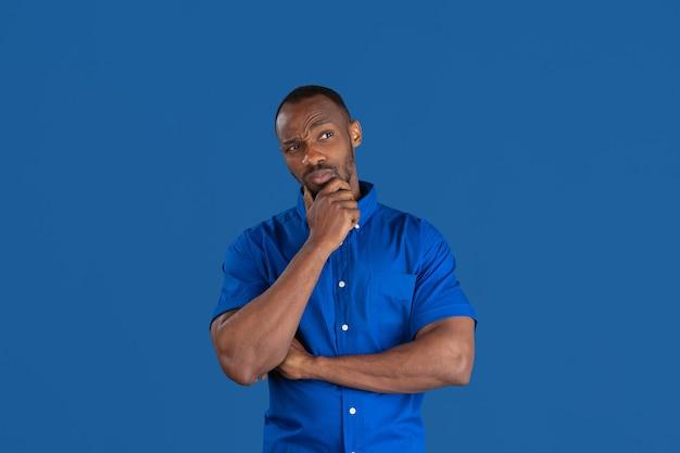 Denken, dromen. zwart-wit portret van jonge afro-amerikaanse man geïsoleerd op blauwe muur.