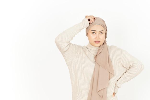 Denken en verward van mooie aziatische vrouw die hijab draagt geïsoleerd op een witte achtergrond