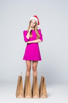 Denken glimlachend meisje in korte roze jurk en hakken nieuwjaar hoed houden papieren boodschappentassen geïsoleerd op een witte achtergrond