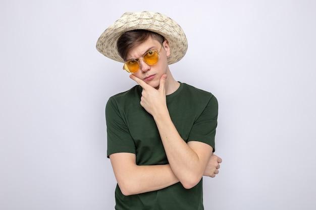 Denken greep kin jonge knappe man met hoed met bril geïsoleerd op een witte muur