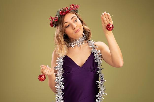 Denken jong mooi meisje dragen paarse jurk en krans met slinger op nek houden en kijken naar kerstboom ballen geïsoleerd op olijf groene achtergrond