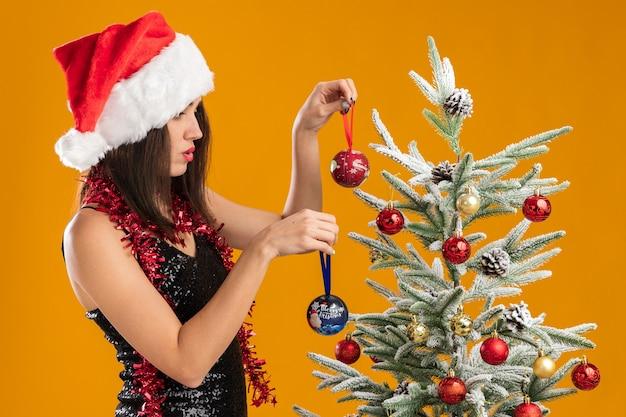 Denken jong mooi meisje met kerstmuts met slinger op nek staande in de buurt van kerstboom houden kerstboom ballen geïsoleerd op een oranje achtergrond