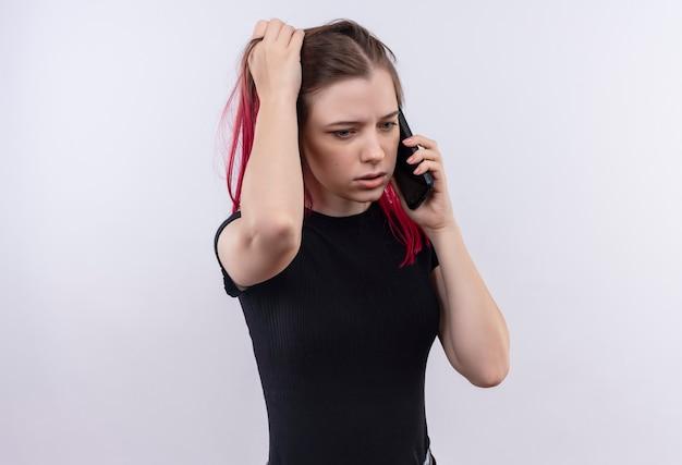 Denken jong mooi meisje met zwarte t-shirt spreekt aan de telefoon greep haar op geïsoleerde witte muur