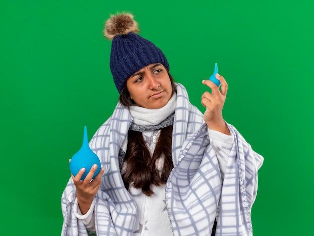 Denken jong ziek meisje dragen winter hoed met sjaal houden en kijken naar klysma's geïsoleerd op groene achtergrond
