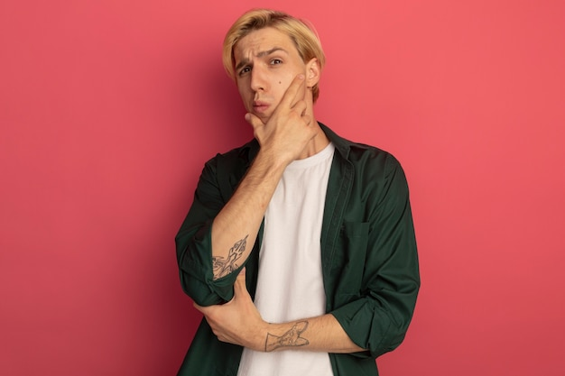 Denken jonge blonde kerel die groen t-shirt draagt dat hand op kin zet