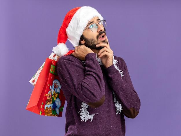 Denken jonge knappe kerel met kerstmuts met slinger op nek houden geschenkzakken op schouder hand zetten wang geïsoleerd op blauwe achtergrond