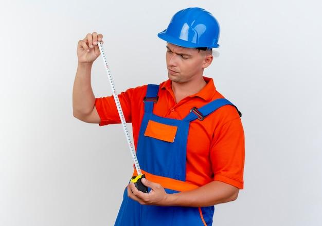 Denken jonge mannelijke bouwer dragen uniform en veiligheidshelm houden en kijken naar meter tape op wit
