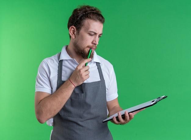 Denken jonge mannelijke kapper dragen uniform houden en kijken naar klembord geïsoleerd op groene achtergrond