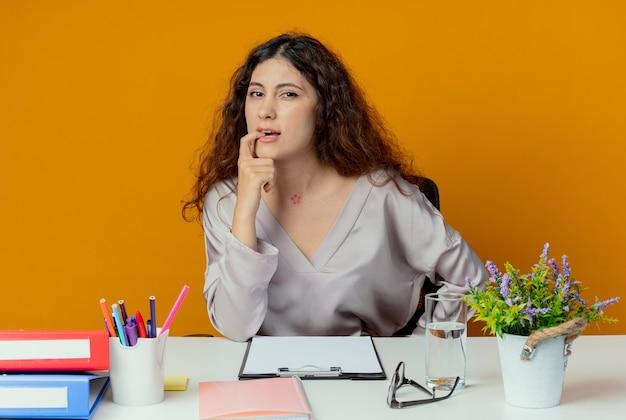 Denken jonge mooie vrouwelijke kantoormedewerker zittend aan een bureau met kantoorhulpmiddelen bijt vinger