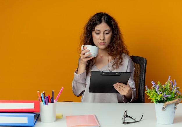 Denken jonge mooie vrouwelijke kantoormedewerker zittend aan een bureau met kantoorhulpmiddelen kopje thee houden en kijken naar klembord in haar hand geïsoleerd op oranje