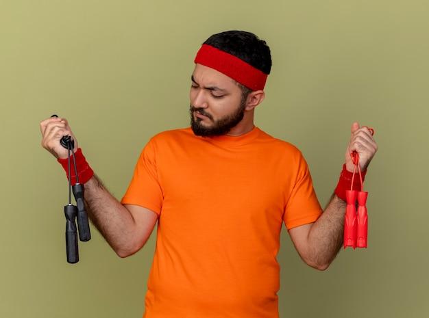 Denken jonge sportieve man met hoofdband en polsbandje houden en kijken naar springtouwen geïsoleerd op olijfgroene achtergrond
