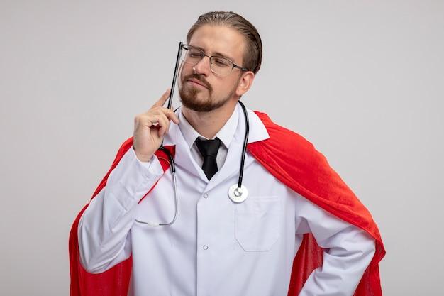 Denken jonge superheld kerel medische gewaad met stethoscoop en bril zetten potlood op wang geïsoleerd op een witte achtergrond