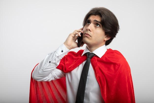 Denken jonge superheld man opzoeken dragen stropdas spreekt op telefoon geïsoleerd op een witte achtergrond
