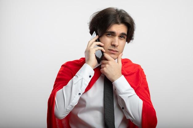 Denken jonge superheld man stropdas dragen spreekt aan de telefoon en hand onder de kin
