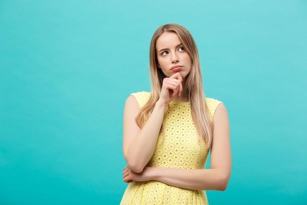 Denken jonge zelfverzekerde vrouw in gele jurk opzoeken geïsoleerd op blauwe achtergrond