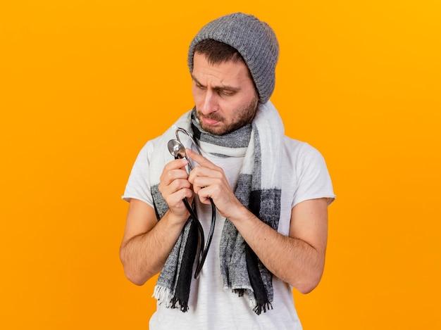 Denken jonge zieke man met winter hoed en sjaal houden en kijken naar stethoscoop geïsoleerd op geel