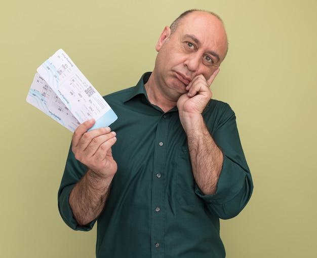 Denken kantelen hoofd man van middelbare leeftijd met groene t-shirt met kaartjes hand op de wang zetten geïsoleerd op olijfgroene muur