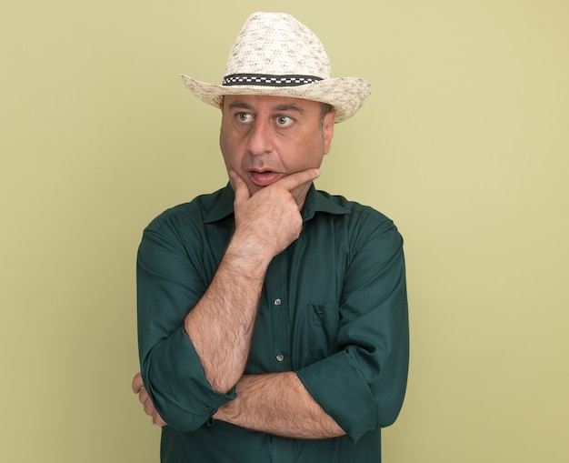 Denken kijken naar de zijkant man van middelbare leeftijd met groene t-shirt en hoed greep kin geïsoleerd op olijfgroene muur