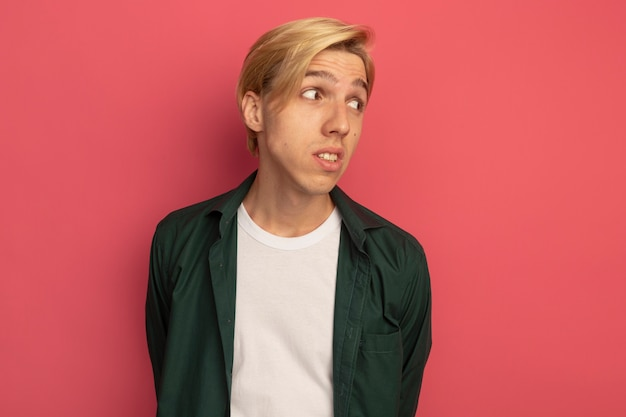 Denken kijken naar kant jonge blonde kerel groene t-shirt dragen