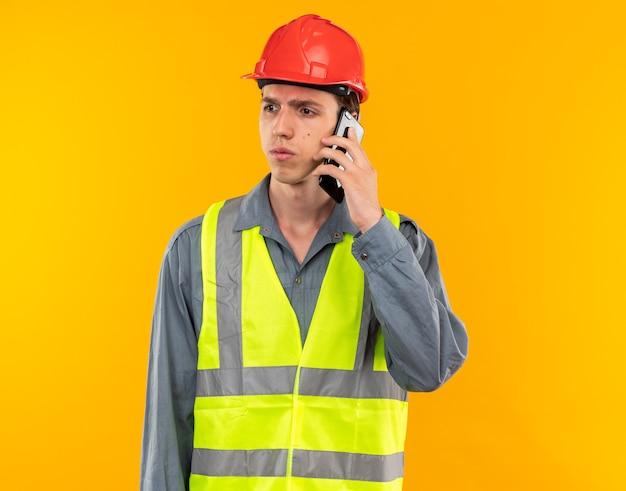 Denken kijkend naar kant jonge bouwer man in uniform spreekt op telefoon geïsoleerd op gele muur