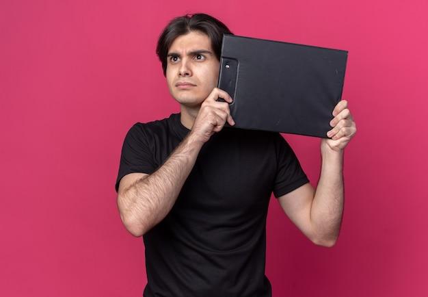Denken kijkende kant jonge knappe kerel die zwarte t-shirt draagt die klembord rond gezicht houdt dat op roze muur wordt geïsoleerd