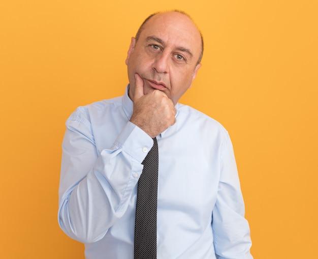 Denken man van middelbare leeftijd met een wit t-shirt met stropdas pakte kin geïsoleerd op oranje muur