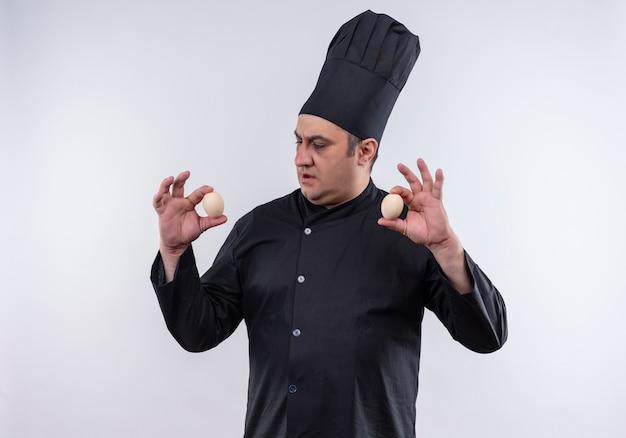 Denken mannelijke kok van middelbare leeftijd in chef-kok uniform uitziende eieren in zijn hand