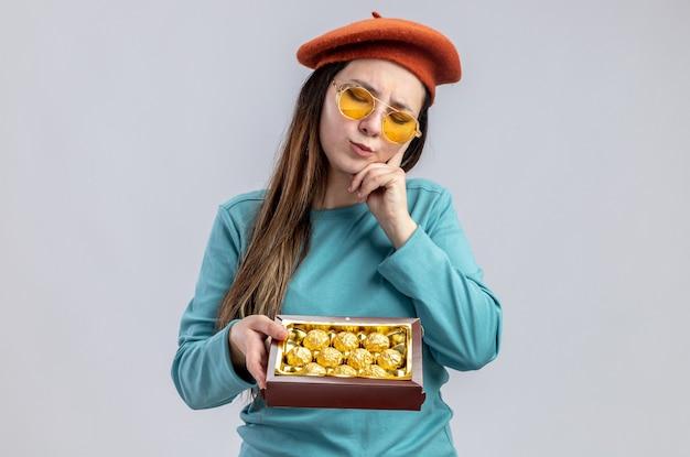 Denken met gesloten ogen jong meisje op valentijnsdag dragen hoed met bril met doos snoepjes hand op wang geïsoleerd op witte achtergrond