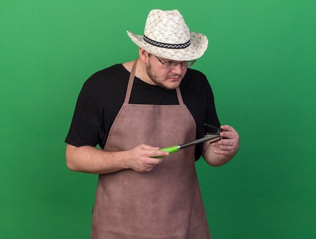 Denken met verlaagd hoofd jonge mannelijke tuinman dragen tuinieren hoed bedrijf en kijken naar schoffel hark geïsoleerd op groene muur