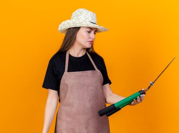 Denken mooi tuinman meisje dragen uniform en tuinieren hoed bedrijf en kijken naar tondeuse geïsoleerd op een oranje achtergrond