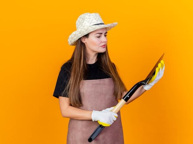 Denken mooi tuinman meisje dragen uniform en tuinieren hoed met handschoenen houden en kijken naar spade geïsoleerd op een oranje achtergrond
