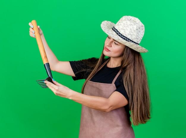 Denken mooi tuinman meisje in uniform dragen tuinieren hoed bedrijf en kijken naar hark geïsoleerd op groene achtergrond
