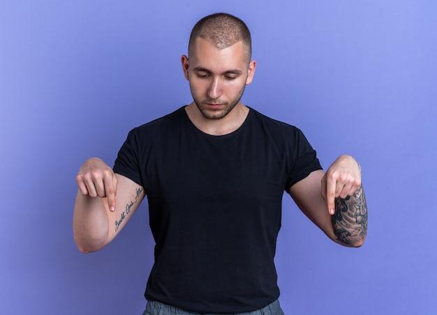 Denken neerkijkend op jonge knappe kerel met zwarte t-shirt wijst naar beneden geïsoleerd op blauwe muur