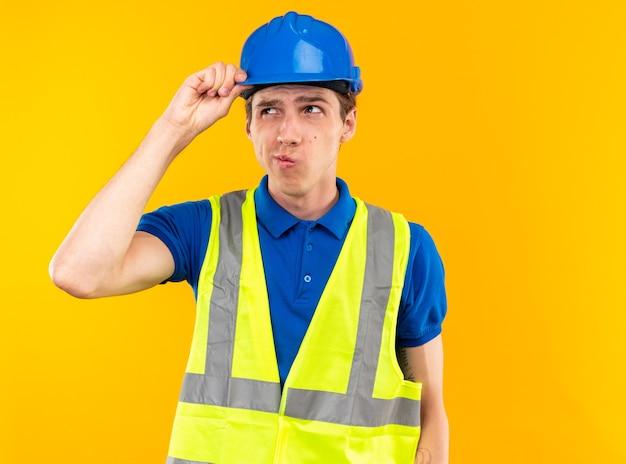 Denken op zoek naar kant jonge bouwer man in uniform geïsoleerd op gele muur