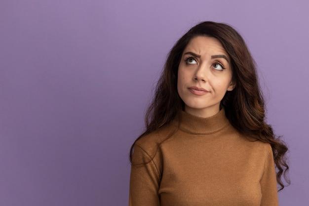 Denken opzoeken jong mooi meisje dragen bruine coltrui geïsoleerd op paarse muur met kopie ruimte