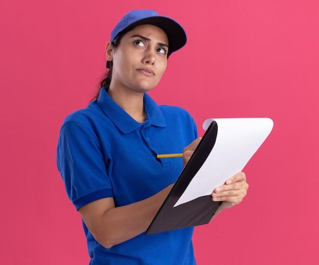 Denken opzoeken van jong leveringsmeisje die eenvormig met glb dragen die iets op klembord schrijven dat op roze muur wordt geïsoleerd