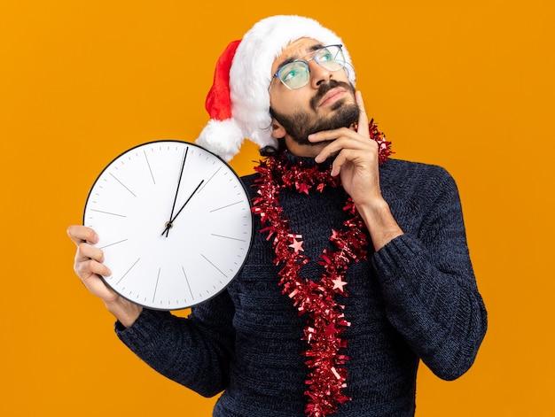 Denken opzoeken van jonge knappe kerel met kerstmuts met slinger op nek houden wandklok hand zetten wang geïsoleerd op een oranje achtergrond