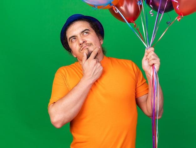 Denken opzoeken van jonge man met feestmuts met ballonnen, greep kin geïsoleerd op groene muur