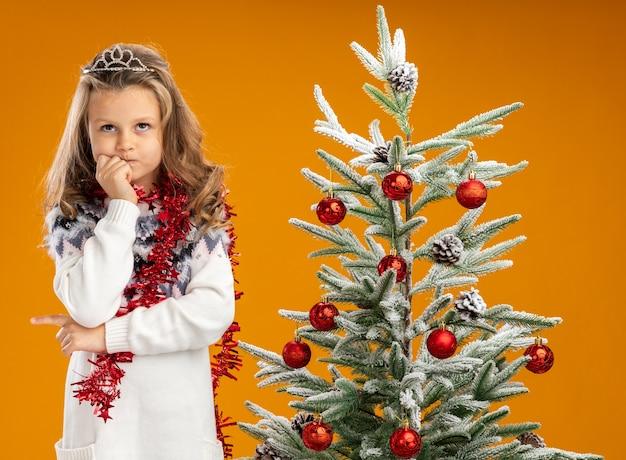 Denken opzoeken van klein meisje permanent in de buurt van kerstboom dragen tiara met slinger op nek hand op kin geïsoleerd op een oranje achtergrond te zetten