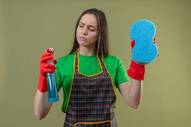 Denken schoonmakend jong meisje die eenvormig in rode handschoenen dragen die schoonmakende spray met spons op geïsoleerde groene muur houden