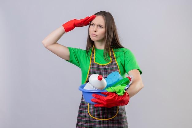 Denken schoonmakend jong meisje die uniform in rode handschoenen dragen die schoonmakende hulpmiddelen houden bekijk distany met hand op geïsoleerde witte muur