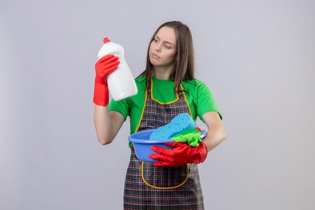 Denken schoonmakend jong meisje die uniform in rode handschoenen dragen die schoonmakende hulpmiddelen houden en reinigingsmiddel op haar hand op geïsoleerde witte muur bekijken