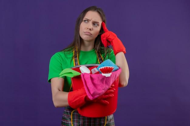 Denken schoonmakend jong meisje die uniform in rode handschoenen dragen die schoonmakende hulpmiddelen houden legde haar vinger op voorhoofd op geïsoleerde purpere muur