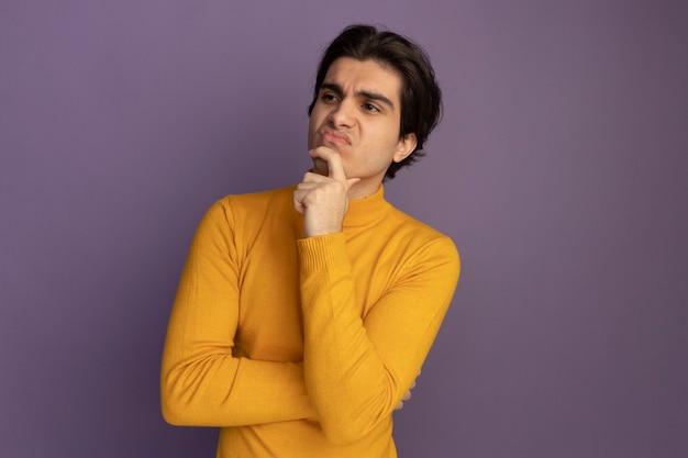 Denken te kijken naar kant jonge knappe kerel die gele coltrui draagt ?? die hand op kin zet die op purpere muur wordt geïsoleerd