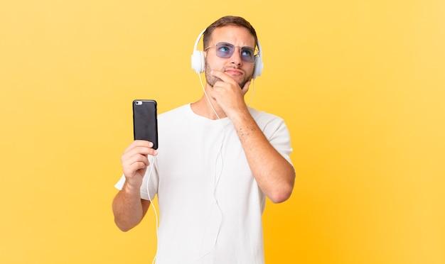 Denken, twijfelachtig en verward voelen, muziek luisteren met koptelefoon en smartphone