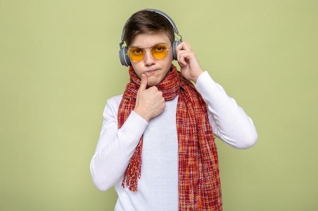 Denken vinger op mond te zetten jonge knappe kerel met sjaal met bril en koptelefoon