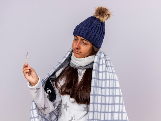 Denken ziek meisje dragen winter hoed met sjaal verpakt in geruite bedrijf en kijken naar thermometer geïsoleerd op een witte achtergrond