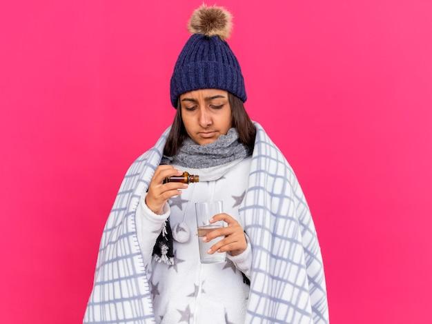 Denken ziek meisje dragen winter hoed met sjaal verpakt in geruite medicament gieten in glas water geïsoleerd op roze achtergrond